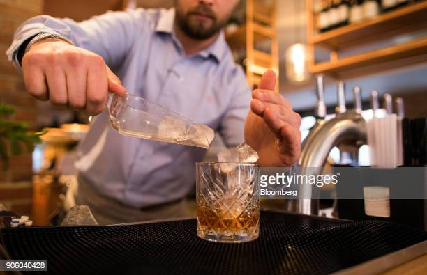 A waiter pours ice into a glass in a Bar and Block restaurant operated by Whitbread Plc in London UK on Wednesday Jan 17 2018 The hotel and...