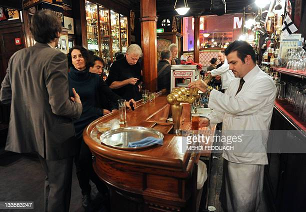 A waiter prepares a beer for a client on November 17 2011 in Paris at the famous Harry's New York Bar where the Bloody Mary the Side Car and other...