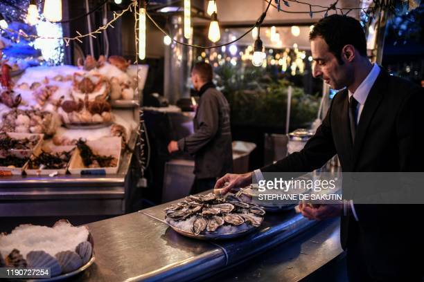 A waiter prepares a sea food platter on December 29 2019 at an oyster bar in Paris