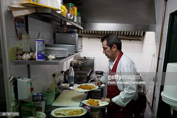 A waiter prepares plates for the lunch of paying clients during the day at Robin Hood restaurant on December 5 2016 in Madrid Spain Association...