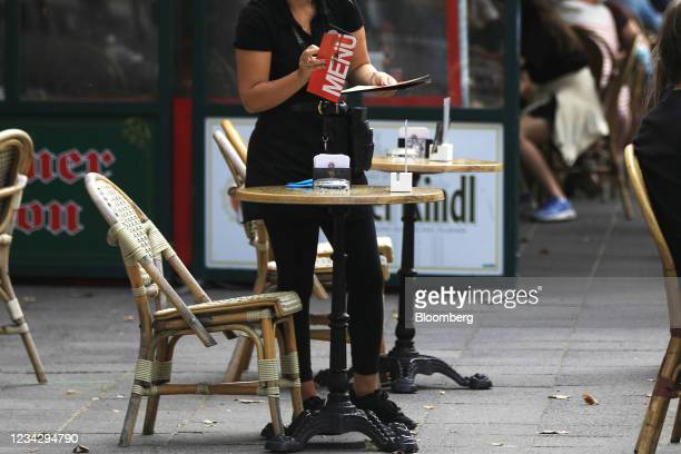 Waiter prepares restaurant terrace table in Berlin, Germany, on Thursday, July 29, 2021. Germany reports gross domestic product figures on July 30....