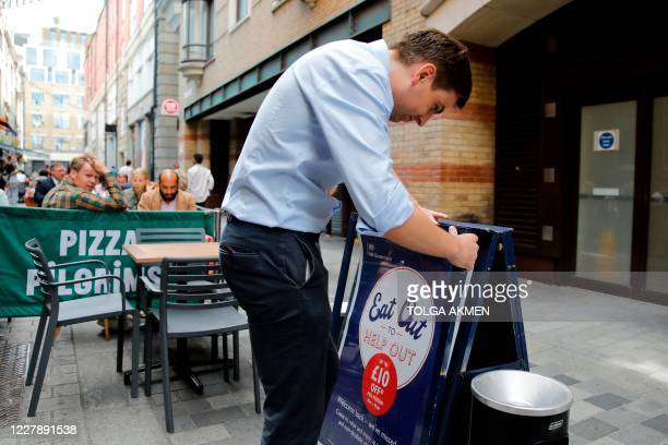 "Waiter prepares signage outside a restaurant in London on August 3 as the Government's ""Eat out to Help out"" coronavirus scheme to get consumers..."