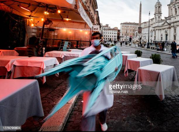 Waiter prepares to close a bar-resturant on Piazza Navona in Rome on October 26 as the country faces a second wave of infections to the Covid-19 . -...