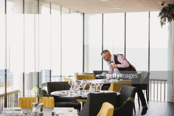 waiter preparing tables in stylish restaurant - waiter stock pictures, royalty-free photos & images