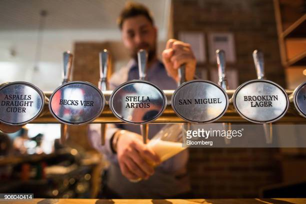 A waiter pulls a pint of lager in a Bar and Block restaurant operated by Whitbread Plc in London UK on Wednesday Jan 17 2018 The hotel and restaurant...