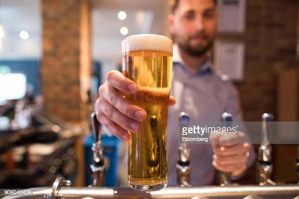 A waiter serves a pint of lager in a Bar and Block restaurant operated by Whitbread Plc in London UK on Wednesday Jan 17 2018 The hotel and...