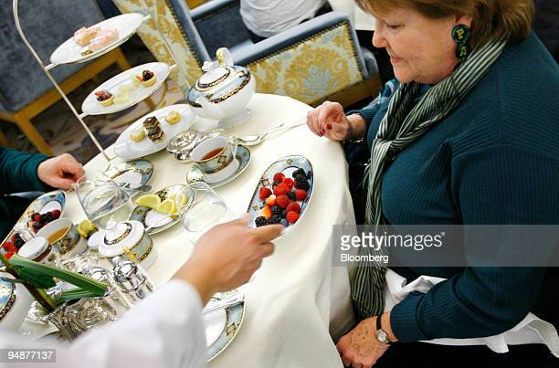 A waiter serves a plate of berries to Patti McGuire during tea service in the Palm Court at the Plaza Hotel in New York US on Monday March 17 2008...