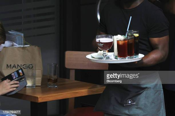 Waiter serves beverages on a restaurant terrace in Berlin, Germany, on Thursday, July 29, 2021. Germany reports gross domestic product figures on...
