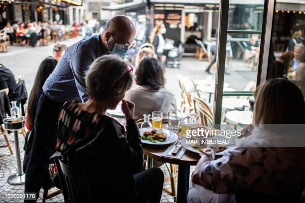 A waiter serves customers at a terrace of a restaurant in Paris on June 15 as cafes and restaurants are allowed to serve customers inside as well as...