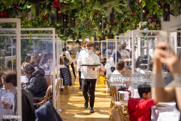 Waiter serves customers at the Alto restaurant inside Selfridges & Co Ltd. Department store in central London, U.K., on Monday, April 12, 2021....