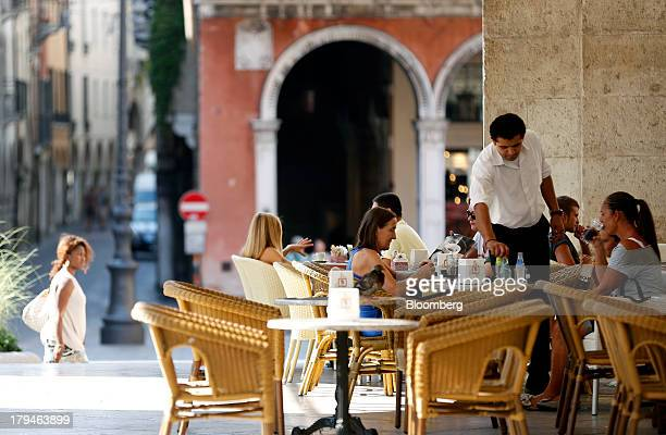 A waiter serves customers their drinks at an outdoor restaurant terrace in Treviso Italy on Tuesday Sept 3 2013 Italy's Agriculture Ministry has...