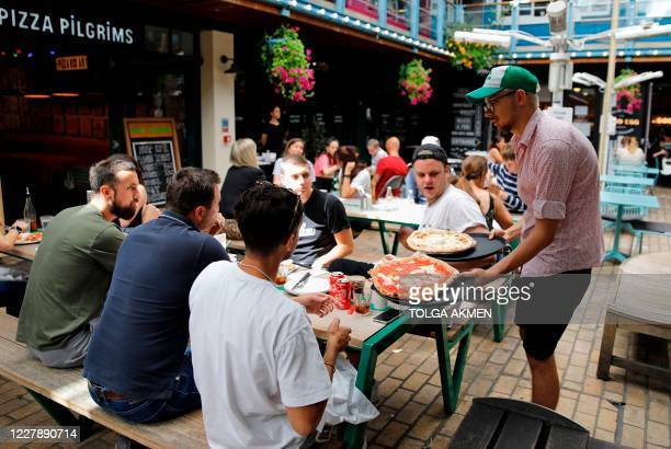 "Waiter serves customers' their pizzas as diners sit at tables outside a restaurant in London on August 3 as the Government's ""Eat out to Help out""..."