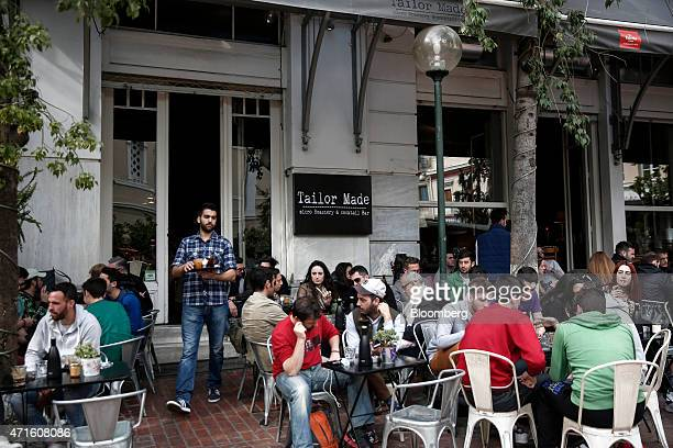 A waiter serves drinks at a cocktail bar previously a fabric store in the Agia Irini district of Athens Greece on Saturday April 25 2015 The downturn...