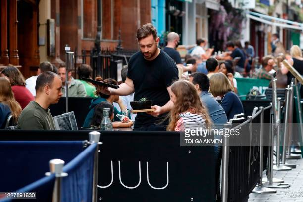 "Waiter serves food to diners sitting at tables outside a restaurant in London on August 3 as the Government's ""Eat out to Help out"" coronavirus..."