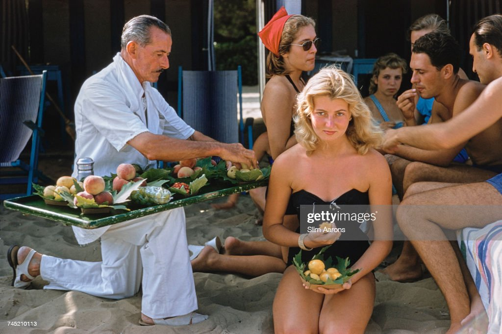 A waiter serves fruit to bathers, including socialite, Louisa del Musso (kneeling), at the Lido in Venice, Italy, 1957.