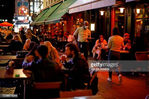 Waiter serves people drinking at the outside tables of a cafe in Soho, in central London on September 23, 2020. - Britain on Tuesday tightened...