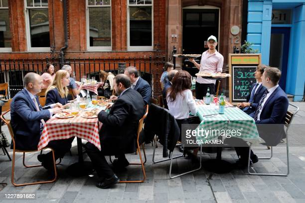 """Waiter serves pizzas as diners sit at tables outside a restaurant in London on August 3 as the Government's """"Eat out to Help out"""" coronavirus scheme..."""