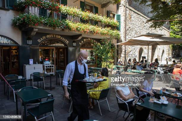 Waiter serves some customers at Bar Marianna, home of the so called 'stracciatella' ice cream flavour, on June 18, 2020 in Bergamo, Italy. The city...