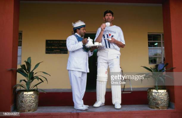 A waiter serves tea to English cricketer Graham Gooch during a match on the England tour of India Delhi January 1992
