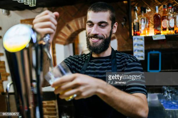 waiter serving a draft beer - ビールサーバー ストックフォトと画像