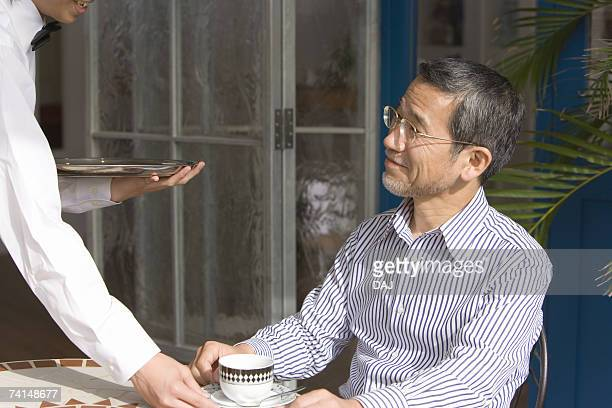 A Waiter Serving a Drink to a Customer, Side View