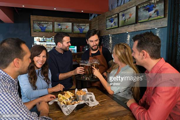 waiter serving a group of friends at the bar - serving sport stock pictures, royalty-free photos & images