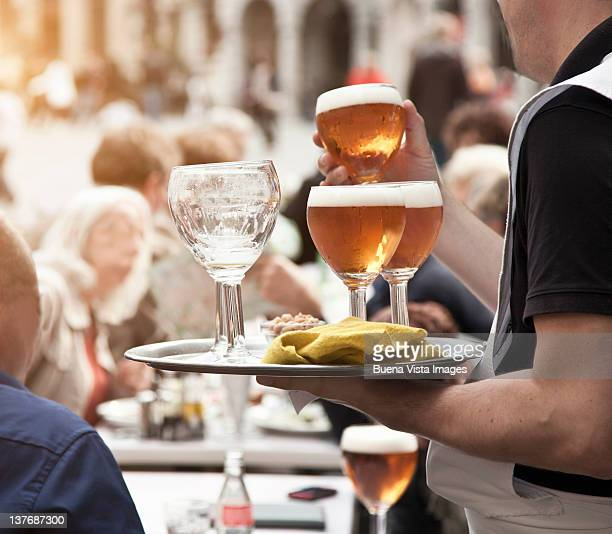 waiter serving beer in brussels - pavement cafe stock pictures, royalty-free photos & images