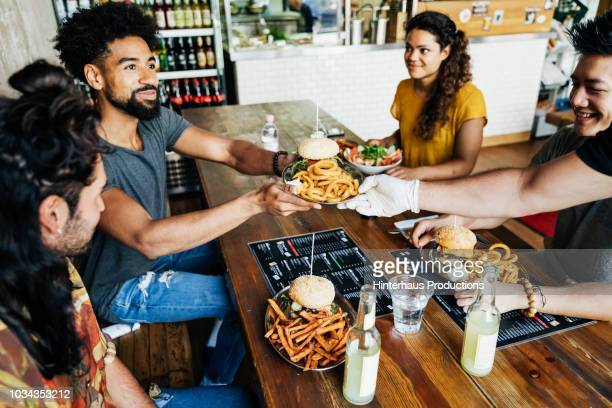 waiter serving burgers to customers - black glove stock pictures, royalty-free photos & images