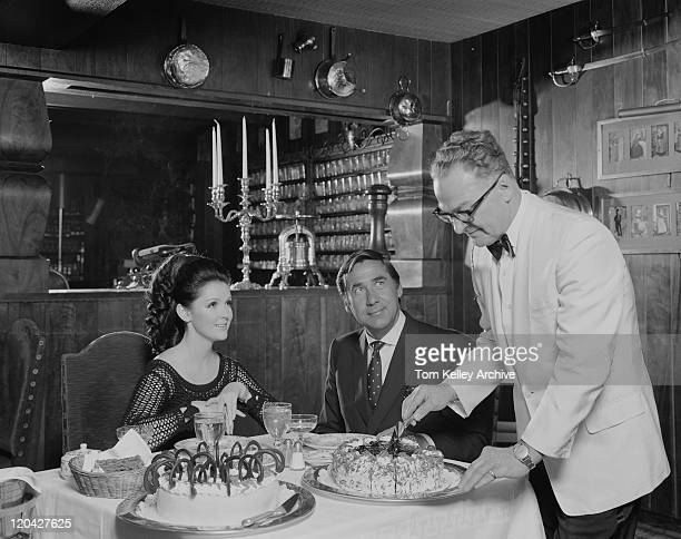 waiter serving cake to couple at table - vintage restaurant stock pictures, royalty-free photos & images