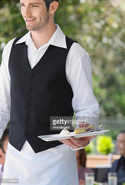 Waiter Serving Cheesecake