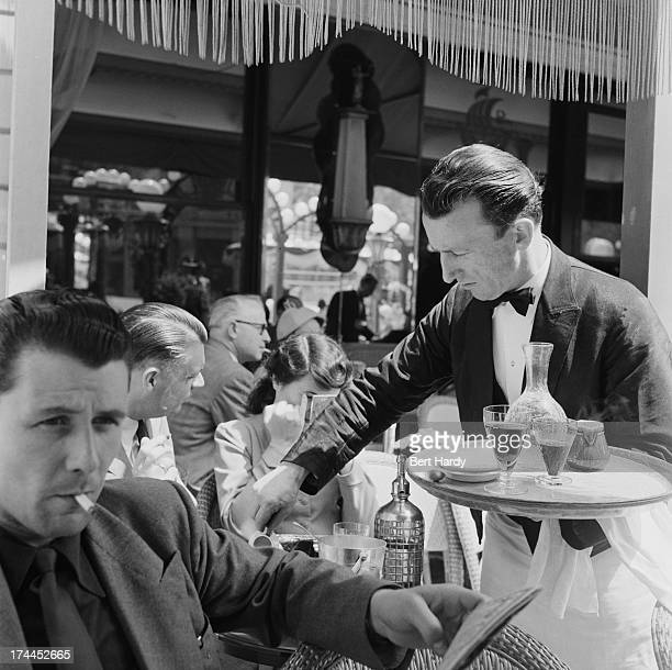 A waiter serving clients on the terrace of a cafe on the ChampsElysees Paris June 1951 Original publication Picture Post 5343 Sunday Morning In The...