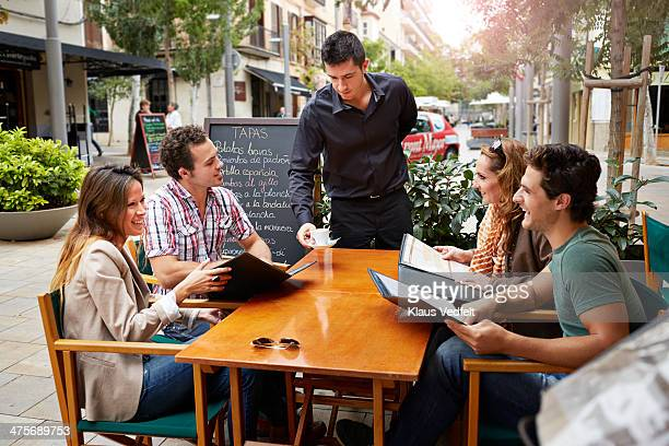 Waiter serving coffee for guests outside