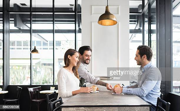 waiter serving coffee to a couple at a cafe - serving size stock photos and pictures