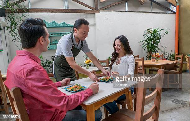 Waiter serving couple at a restaurant