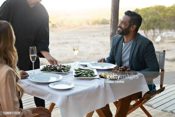 waiter serving couple at private romantic dinner in luxury cabin - finanzen und wirtschaft stock-fotos und bilder