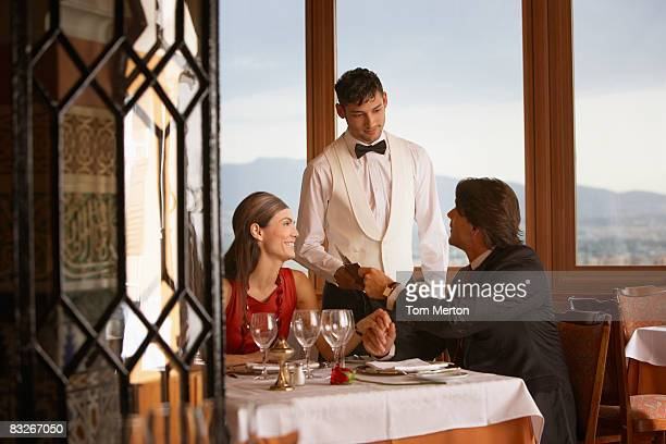 waiter serving couple in elegant restaurant - elegantie stockfoto's en -beelden
