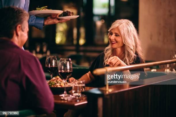 Waiter serving dinner to senior couple at fine dining restaurant