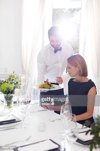 Waiter serving dinner to woman in elegant restaurant