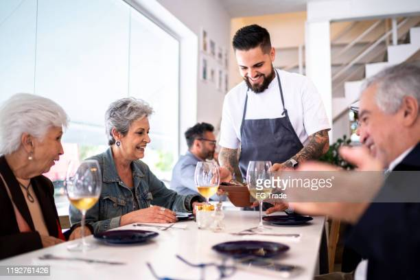 waiter serving dish to a group of customers in a restaurant - explaining stock pictures, royalty-free photos & images