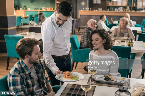 Waiter serving dishes to couple sitting at table in restaurant