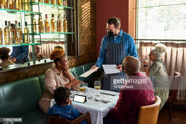 waiter serving family in restaurant - table stock pictures, royalty-free photos & images