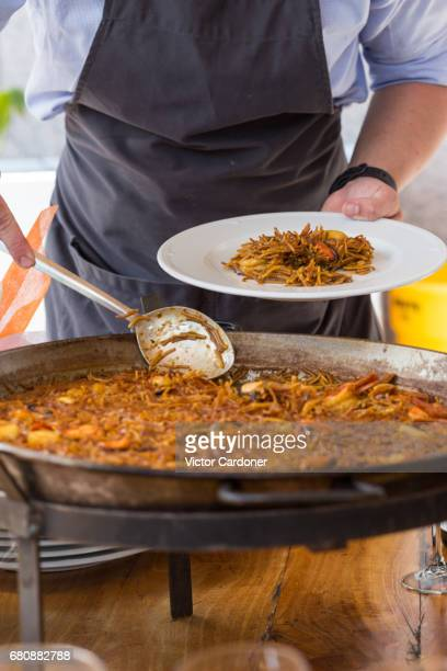 waiter serving fideuà - paella stock photos and pictures