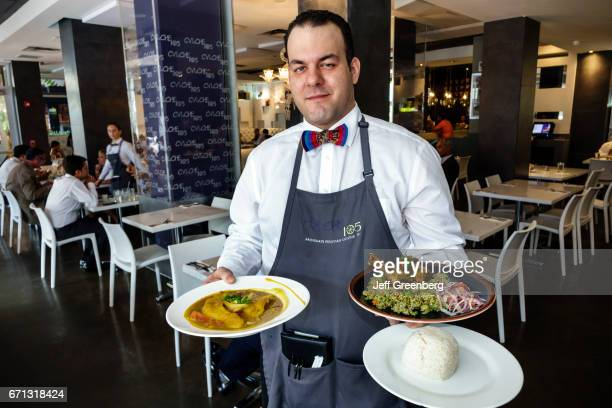 A waiter serving food at Cviche 105