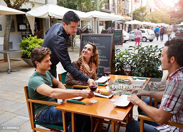 waiter serving food for guests at restaurant - klaus vedfelt mallorca stock pictures, royalty-free photos & images