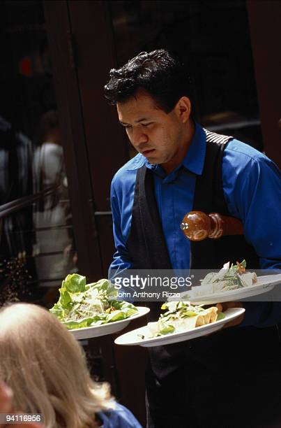 Waiter serving food in outdoor cafe