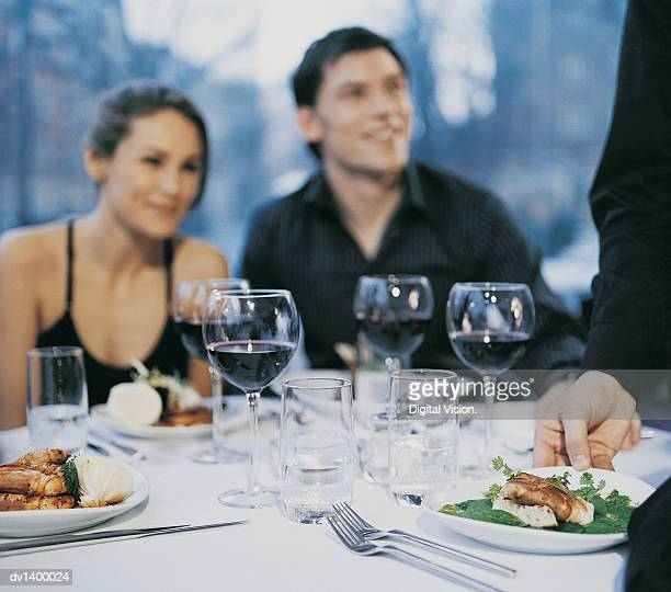 Waiter Serving Food to a Couple Seated in a Restaurant