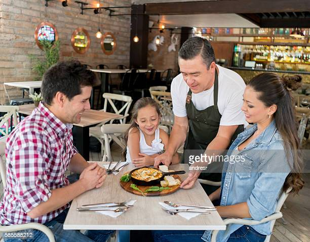 Waiter serving food to a family at restaurant