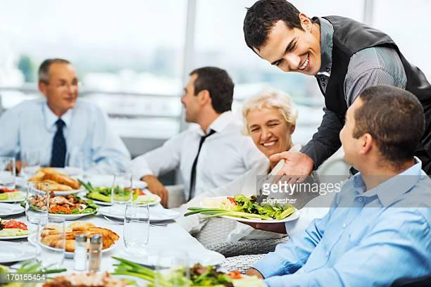 Garçon de café servant des repas pour un groupe de gens d'affaires.