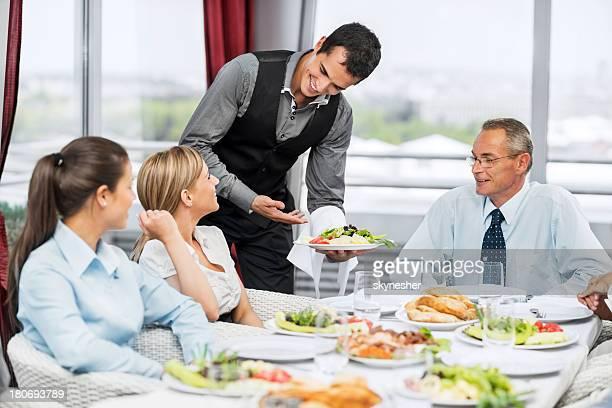 Mesero que sirve comidas para un grupo de empresarios.