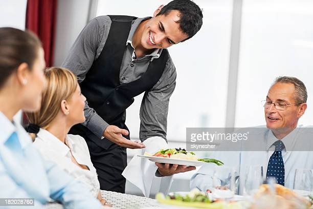 Waiter serving food to a group of businesspeople.